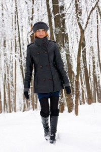 Beautiful ginger-haired girl going in the snowy forest